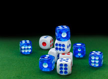 Blue and white dices on the green velvet surface royalty free stock images