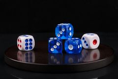 Blue and white dices on a round stone base. black background stock photo