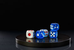 Blue and white dices on a round stone base stock photo