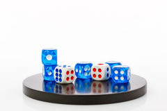 Blue and white dices on a round stone base stock images