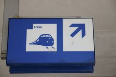 Blue and white direction sign to platforms for the trains. Trein in Dutch with old icon with a hondenkop or MAT64 trainn royalty free stock photo