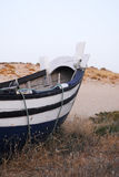 Blue and White Fishing Boat on Sand Dune, Beach Royalty Free Stock Images