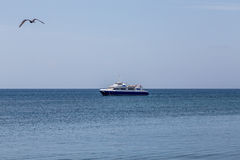 Blue and White Fishing Boat Morred on Sea stock images