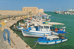 Blue and white fishing boats with medieval fortress. Small blue and white fishing boats moored at Koules Fortress in Heraklion, Crete, Greece Stock Image