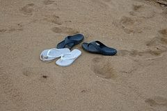 BLUE AND WHITE FLIPFLOPS ON THE SAND Stock Photography