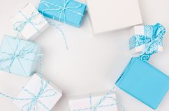 Blue and white gift boxes with ribbon. Light blue and white gift boxes with ribbon on white table. Holiday concept, copy space royalty free stock photography