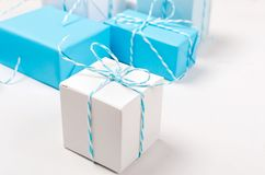 Blue and white gift boxes with ribbon. Light blue and white gift boxes with ribbon on white table. Holiday concept, copy space stock photos