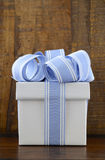Blue and white gift on dark wood background. Stock Photos