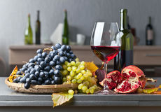 Blue and white grapes with glass of wine. On a kitchen table Stock Photography