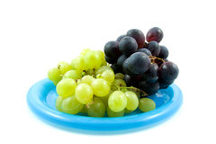 Blue and white grapes on plate Royalty Free Stock Photography