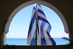 Blue and white Greek flag through archway with sea view on Greek Island. Blue and white Greek flag flying from archway overlooking the Mediterranean on Kos stock photo