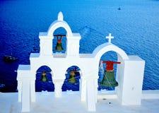Famous white church in Santorini with church bells against sea. Oia, Greece. stock photos