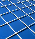 Blue and white grid. White metal grid on blue background stock images