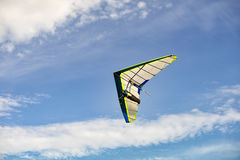 Blue and white hang glider in flight off with blue sky Stock Photo