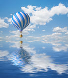 Blue-white Hot Air Balloon in the sky. 3d Blue-white Hot Air Balloon in the blue sky and reflection in water Royalty Free Stock Photography