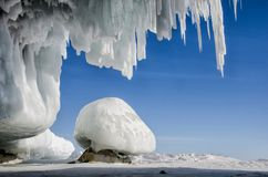 Blue white ice cave with icicle stalactites, blue sky and stone covered ice. Near lake Baikal stock photography