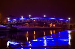 Blue illuminated bridge over the river. Blue and white illuminated bridge over the river at night during winter Stock Images