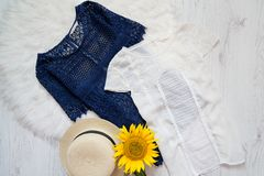 Blue and white lace blouse. Hat and sunflower on white fur. Fashionable concept, top view Royalty Free Stock Photo