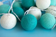 Blue and white light ball made of yarn threads closeup on the blue background. Royalty Free Stock Photo