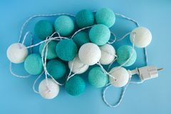 Blue and white light ball made of yarn threads closeup on the blue background, top view. Stock Photos