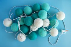Blue and white light ball made of yarn threads closeup on the blue background, top view. Stock Image