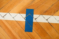 Blue white lines. Worn out wooden floor of sports hall with colorful marking lines. Stock Photo