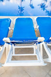 Blue and white lounges near pool Stock Photos