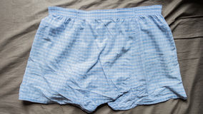 Blue and white mini pant on bed. A blue and white mini pant on bed Stock Photo