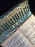 Blue and white mother of pearl accordion with music 6. Accordion with blue and white mother of pearl finish on  red leather couch with Polka music score by Stock Photo