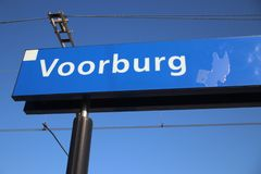 Blue and white name sign Voorburg on the platform of the railway station in the Netherlands. Blue and white name sign Voorburg on the platform of the railway royalty free stock photography