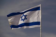 The blue and white national flag of Israel. Blowing in the wind on blue sky background Stock Photos