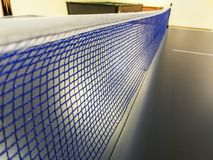 Blue and white net of a blue ping pong table in a game room. In a games room of many residences or Italian hotels you will find table tennis, table football, and royalty free stock photo
