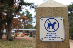 Blue and white No Dogs Permitted In Playground Area sign with play equipment blurred in the background royalty free stock images