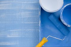 Blue and white paint in cans top view. roller with a yellow handle for painting walls royalty free stock image