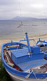 Blue and white painted boat. S pulled out of the sea onto the beach royalty free stock photos