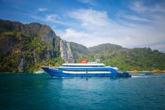 Blue and white passenger ferry ship sailing to destination point. Port with another ships and mountain on background.  stock images