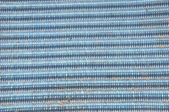 Blue and white pattern. Pattern of woven blue and white plastic, with sand grains Royalty Free Stock Photo