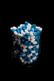 Blue and white pills in a glass on black background Royalty Free Stock Photo