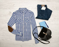 Blue and white plaid shirt, jeans, mobile phone, notebook with pen and black bag. Wooden background. Fashionable concept Stock Images