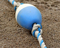 Blue and white plastic BUOY laying on sand at beach Royalty Free Stock Photos