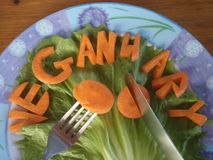 A blue and white plate of carrot spelling veganuary royalty free stock photos