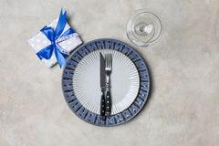 Blue and white plate dish with present box for men with fork and knife, wine glass at white background royalty free stock image