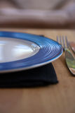Blue and White Plate with Fork. And black napkin on a wooden table Stock Photography