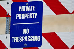 Blue and White Private Property Sign on Construction Barricade. Blue and White Private Property and No Trespassing Sign on Construction Barricade royalty free stock photography