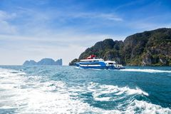 Blue with white and red accents pleasure speed boat. Sailing on the sea against a tropical island. Rear view. Motor track and royalty free stock photography