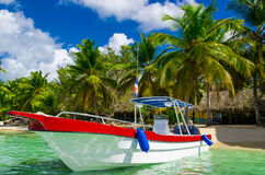 Blue, white, red boat on azure water among palm trees