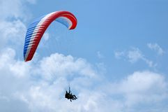 Blue, white and red paragliding. Baptism with an instructor through clouds (Franch Alps Royalty Free Stock Photos