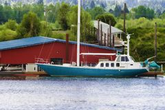 Blue and white sailboat docked on the Willamette River in Oregon. Blue and white sailboat is docked next to a red building along the Willamette River at Sauvie royalty free stock photo