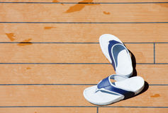 Blue and White Sandles on a Wood Deck. A pair of blue and white sandles on a wood deck with drips of water royalty free stock photo