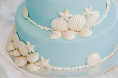 Blue and White Seashell Cake. A wedding cake adorned in white seashells, starfish, and pearls royalty free stock image